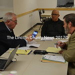 Bankruptcy trustee Pat Perrino reviews pictures of the Clary Lake Dam with Paul Kelley (right), of Pleasant Pond Mill LLC, as Robert Rubin looks on during a meeting of the company's creditor ...